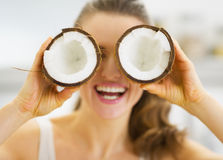 Smiling woman holding two pieces of coconut in front of eyes Royalty Free Stock Photo