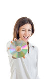 Smiling woman holding up compact disc or cd  and looking at came Stock Photo