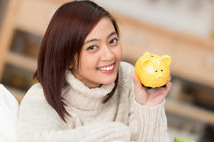 Smiling woman holding up a yellow piggy bank Royalty Free Stock Photos