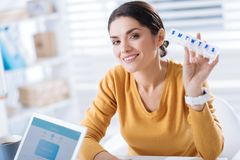 Smiling woman holding a useful pillbox and feeling glad to recover. Cheerful woman. Recovered cheerful young woman sitting with a pillbox in her hand and feeling royalty free stock image