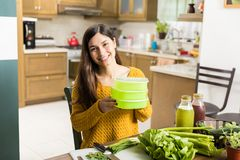 Smiling Woman Holding Vegetable Containers At Home. Portrait of fresh looking woman holding plastic containers with veggies on table royalty free stock photos