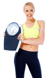 Smiling woman holding a waight scale. Smiling woman holding a weight scale while posing on white background royalty free stock images