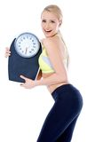 Smiling woman holding a waight scale Stock Photo