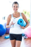 Smiling woman holding water bottle and yoga mat Stock Images