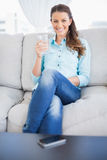Smiling woman holding water glass sitting on sofa Stock Photos
