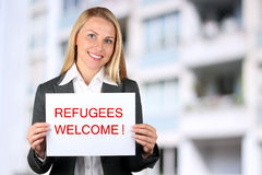 Smiling woman holding a white banner with words welcome refugees.  royalty free stock photography