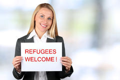 Smiling woman holding a white banner with words welcome refugees. Blue background behind royalty free stock photos