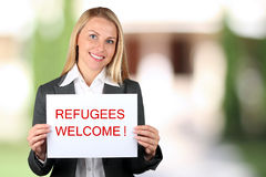 Smiling woman holding a white banner with words welcome refugees. Green background behind stock images