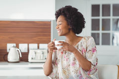 Smiling woman holding white cup. In the kitchen Stock Photos
