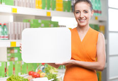 Smiling woman holding a white sign at supermarket Royalty Free Stock Photography