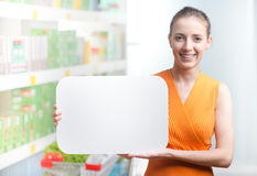 Smiling woman holding a white sign at supermarket Royalty Free Stock Image