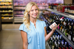 Smiling woman holding wine bottle Royalty Free Stock Images
