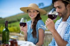 Smiling woman holding wineglass while sitting with man Stock Photos