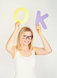 Smiling woman is holding the word ok Royalty Free Stock Images