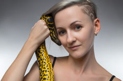 Smiling woman holding yellow snake Stock Images