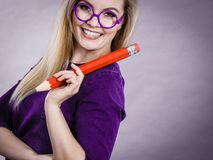 Smiling woman holds big pencil in hand Stock Photos