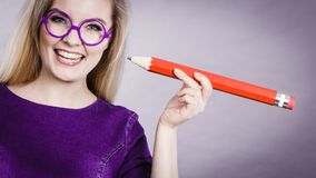 Smiling woman holds big pencil in hand stock image