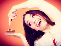 Smiling woman holds cake in hand Royalty Free Stock Images