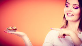 Smiling woman holds cake in hand pointing with finger Stock Photo
