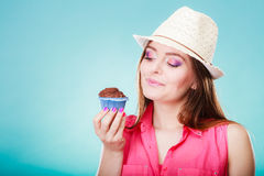 Smiling woman holds chocolate cake in hand. Sweet food sugar make us happy. Smiling woman summer clothing holds cake chocolate muffin in hand blue background Royalty Free Stock Image