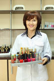 Smiling woman holds colored nail polish Royalty Free Stock Image