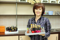 Smiling woman holds colored nail polish on stand Stock Photography