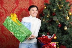 Smiling woman holds gifts near Christmas tree Royalty Free Stock Photography
