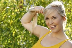 Smiling woman holds her blond hair Stock Photo