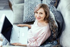 Smiling woman holds a laptop working from home. Charming Mature Woman Works From Home. Smiling Woman With A Laptop On Her Knees Looks At Camera. Top View stock photos