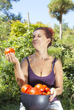 Smiling woman holds organic tomato Royalty Free Stock Photos