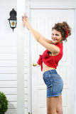 Smiling woman holds pole next to white entrance door Royalty Free Stock Photography