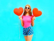Smiling woman holds a red air balloons in the shape of a heart Royalty Free Stock Photos