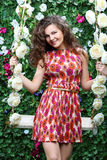 Smiling woman holds swing overgrown with flowers. Next to green hedge with flowers Stock Photography