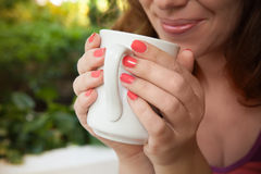 Smiling woman holds white cup of coffee in her hands Stock Images