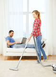 Smiling woman with hoover and man with laptop Stock Photography