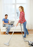 Smiling woman with hoover and man with laptop Royalty Free Stock Image