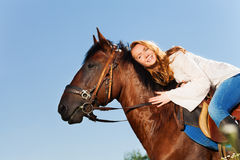 Smiling woman hugging beautiful bay horse Stock Images