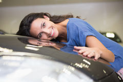 Smiling woman hugging a black car. At new car showroom Stock Photography