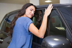 Smiling woman hugging a black car. At new car showroom Stock Images