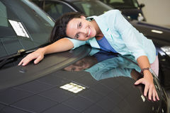 Smiling woman hugging a black car. At new car showroom Stock Image