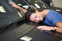 Smiling woman hugging a black car. At new car showroom Royalty Free Stock Photos