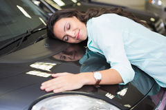 Smiling woman hugging a black car. At new car showroom Royalty Free Stock Images
