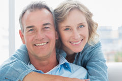Smiling woman hugging her husband on the couch from behind Royalty Free Stock Photo