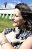Smiling woman hugging pug puppy Stock Photography