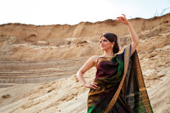Smiling woman in indian sari against the sand background Stock Images