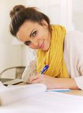 Smiling Woman Indoor Writing on Her Notepad Royalty Free Stock Images