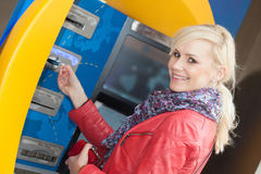 Smiling woman inserting her card in an ATM Royalty Free Stock Photos