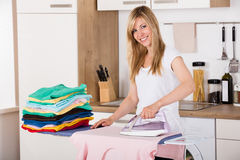 Smiling Woman Ironing Clothes With Electric Iron. Young Smiling Woman Ironing Clothes With Electric Iron At Home Royalty Free Stock Image