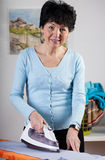 Smiling woman ironing Royalty Free Stock Image