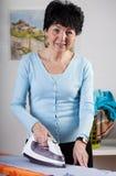 Smiling woman ironing Royalty Free Stock Photo